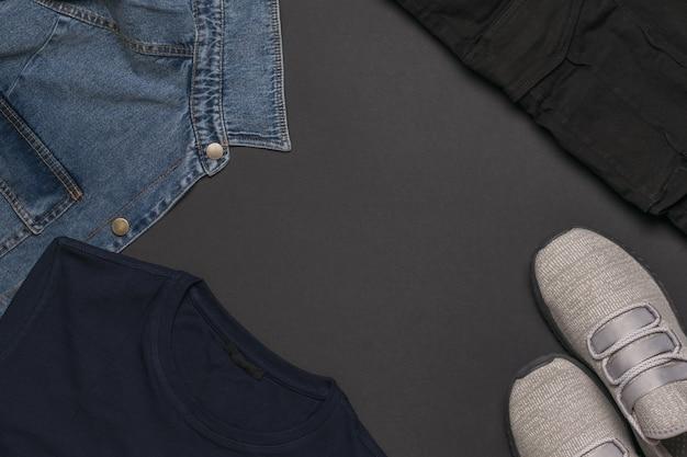 Ein satz freizeitkleidung und turnschuhe für männer auf einem schwarzen hintergrund. modische freizeitkleidung für jugendliche. flach liegen.
