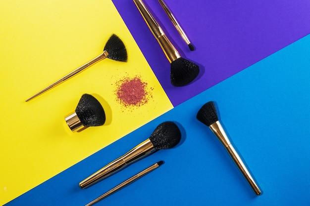 Ein satz goldpinsel zum auftragen von make-up und lidschatten auf dem augenlid befindet sich auf einem farbigen hintergrund, draufsicht: designkonzept, make-up, schönheitssalon