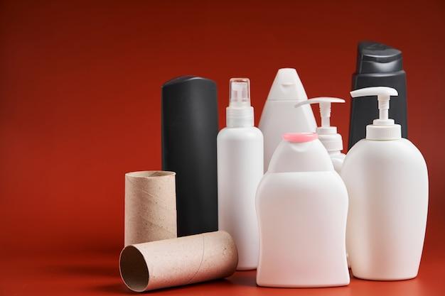 Ein satz leerer, sauberer plastikbehälter in verschiedenen formen aus haushaltsreinigungsmitteln, duschutensilien und toilettenpapierkartonröhrchen