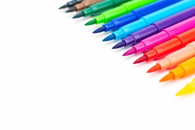 Ein satz mehrfarbiger filzstifte auf weißem hintergrund. zeichenmarkierungen, bleistifte, regenbogentinte, künstlerwerkzeuge, kreative verfolgung, freizeit, hobby. bunte schulsachen hautnah. rechte seitenansicht.