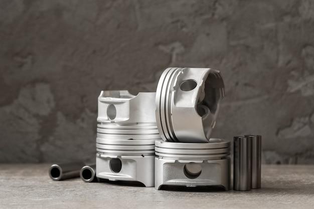 Ein satz neuer kolben zum reparieren von autobremsen auf grauem betonhintergrund, kopierraum.