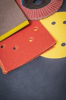 Ein satz schleifwerkzeuge und braunes sandpapier auf einem schwarzen werkstatttisch-assistenten wird zum schleifen von gegenständen verwendet