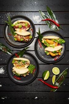 Ein satz von drei asiatischen gerichten auf schwarzen tellern auf einem holztisch, dekoriert mit limette, chili und mehl. appetitliches bao mit gemüse und fleisch