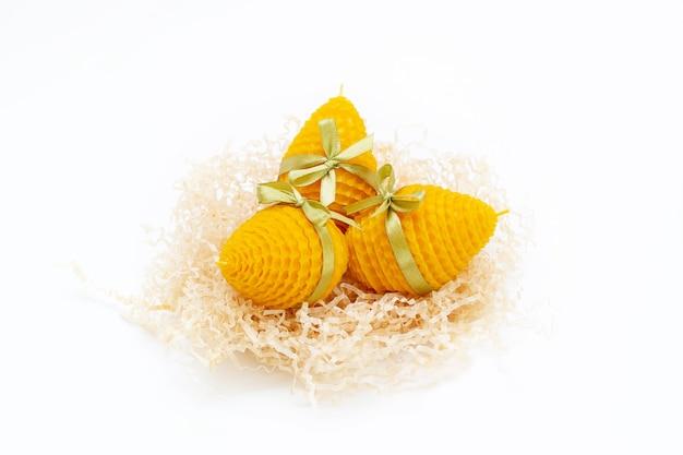 Ein satz von drei gelben dekorativen natürlichen bienenwachskerzen mit einem honigaroma für den innenraum in form eines ostereies