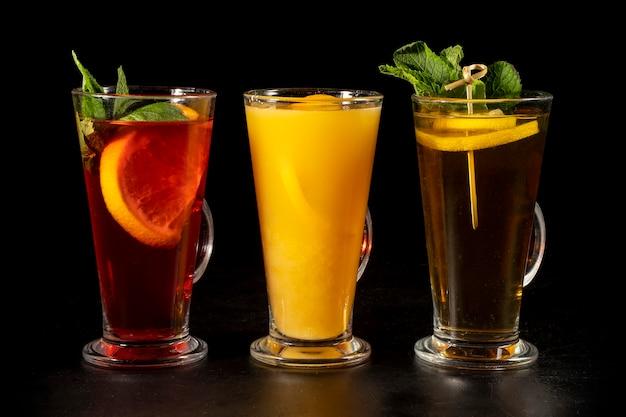 Ein satz von drei heißen teegetränken mit zitrone und frisch gepresstem orangensaft. heiße wärmende getränke auf einem schwarzen hintergrund