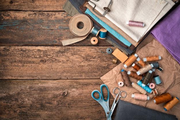 Ein satz von stoffen, fäden und anderem nähzubehör auf einem hölzernen hintergrund.