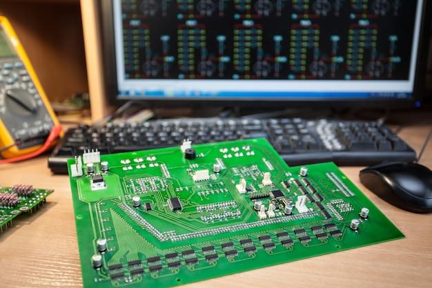 Ein satz von widerständen auf der halbleiterplatte auf dem tisch ist ein funktechniker vor dem computer und dem multimeter