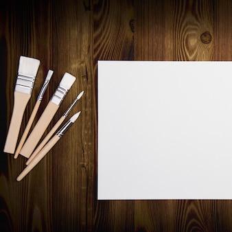Ein sauberes weißes blatt und pinsel auf einer holzoberfläche mit platz zum kopieren.