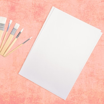 Ein sauberes weißes blatt und pinsel auf einer strukturierten rosa oberfläche mit platz zum kopieren.