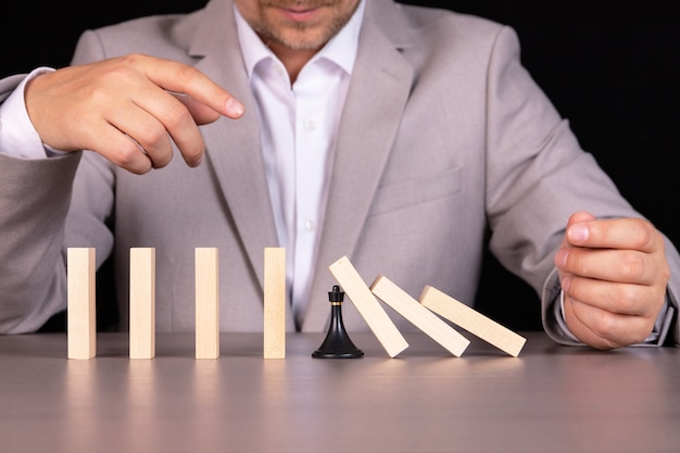 Ein schachbauern verhindert, dass ein hölzerner dominostein fällt