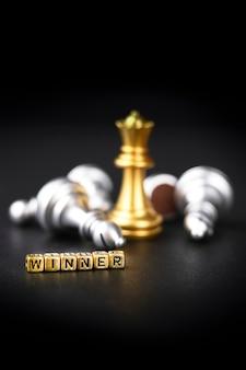 Ein schachbrettspiel. das erfolgreiche geschäftskonzept: wettbewerb und management. eine goldene schachfigur auf dunklem hintergrund. wortsieger. kopieren sie platz für text.