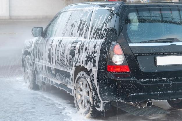 Ein schaum, der bei einer autowaschanlage von einem schwarzen auto abgewaschen wird.