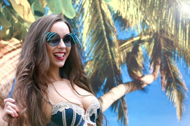 Ein schickes langhaariges mädchenmodell in einem badeanzug auf einem tropischen hintergrund flirtet.tropische schönheit