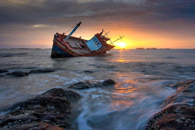 Ein schiffswrack am meer während des sonnenuntergangs festgemacht