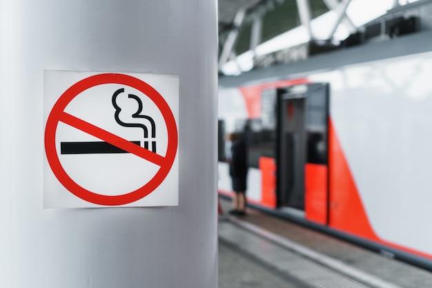 Ein schild, das das rauchen auf einer stange in der nähe des bahnsteigs verbietet.