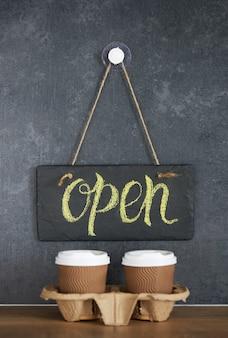 Ein schild mit der aufschrift open on cafe auf einer schwarzen kreidetafel. nach der quarantäne. kaffeegläser zum mitnehmen im dunkeln. geschäftseröffnung