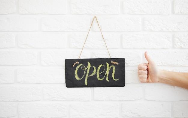 Ein schild mit der aufschrift open on cafe oder restaurant hängt an der tür am eingang. nach der quarantäne. hand zeigt daumen hoch