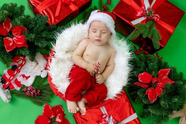 Ein schlafendes kind in einem weihnachtsmannkostüm liegt mit einer süßigkeit in den händen auf einem grün