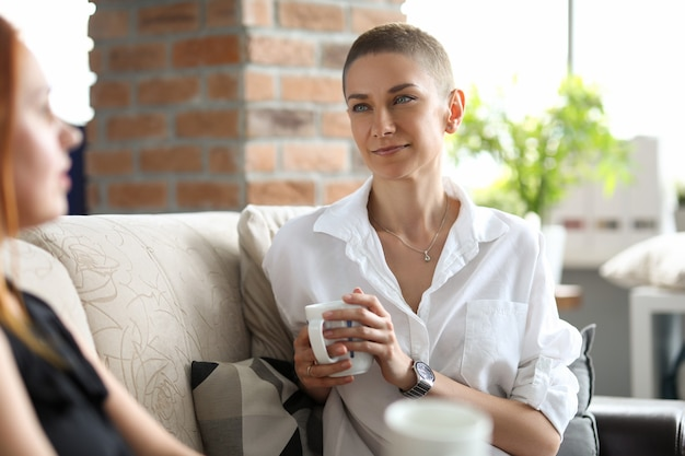 Ein schlankes mädchen in einer weißen bluse sitzt auf einem sofa und trinkt mit ihrer freundin kaffee. kreative junge frau, die im büro während des mittagessens ruht