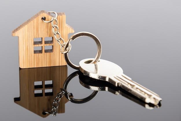 Ein schlüssel an einem haus geformt holz schlüsselanhänger
