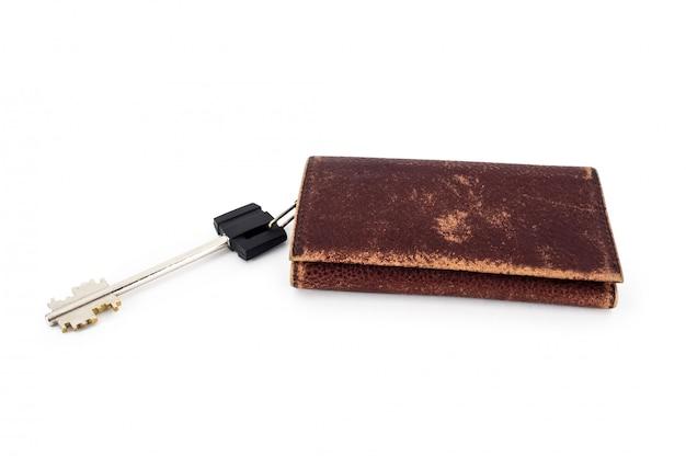 Ein schlüssel und ein zerkratzter schlüsselhalter aus braunem leder