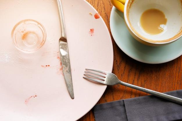 Ein schmutziger teller mit marmeladenresten, schmutzigem besteck und einer tasse kaffee im restaurant.