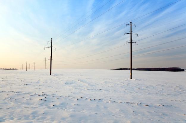 Ein schneebedecktes feld im winter. an den sichtbaren strommasten. sonnenuntergang