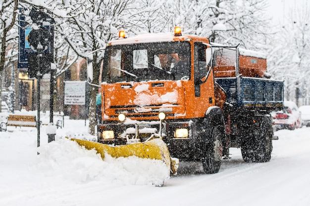 Ein schneepflug bei der arbeit während des schneefalls auf weiß getünchten straßen in der stadt
