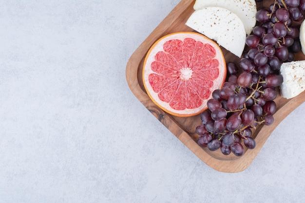 Ein schneidebrett voller käse, grapefruit und trauben. foto in hoher qualität