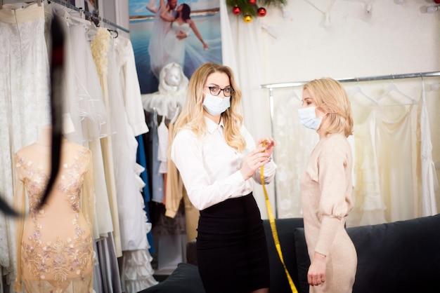 Ein schneider arbeitet während der coronavirus-pandemie mit einem kunden in seinem atelier zusammen und trägt schutzmasken im gesicht.