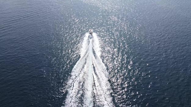 Ein schnellboot rast vorwärts auf dem wasser des blauen meeres. boot im meerblick von der drohne.