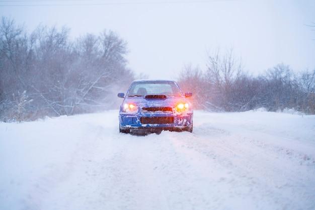 Ein schneller blauer sportwagen am verschneiten wintertag, in der kalten jahreszeit, auf der straße
