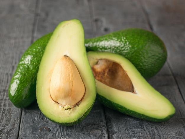 Ein schnitt und zwei ganze avocados auf einem holztisch.