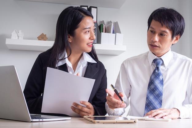 Ein schöner asiatischer bankier beschreibt investitionen und gewinne aus dem kauf des indexfonds. finanzberater