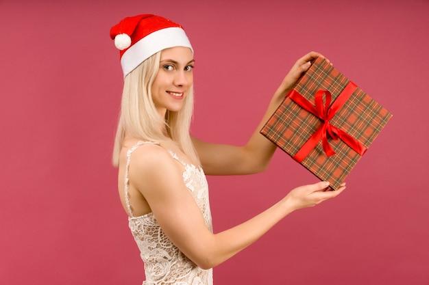 Ein schöner athletischer transgender-mann in einem neujahrshut und einem weißen kleid, halten in den händen geschenke. feier von weihnachten oder neujahr auf rubinhintergrund