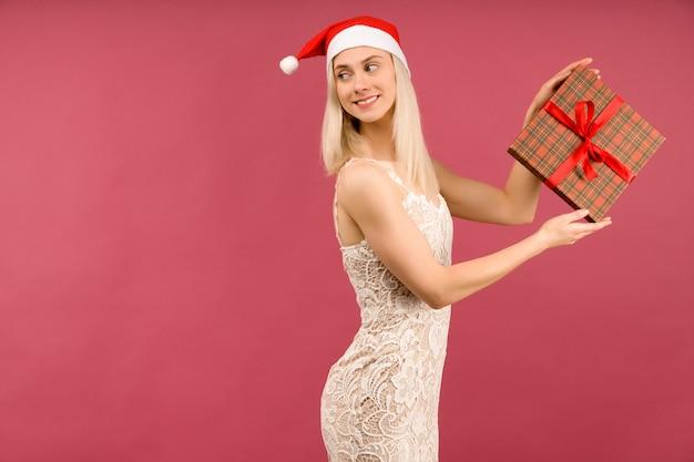 Ein schöner athletischer transgender-mann in einem neujahrshut und einem weißen kleid, halten in den händen geschenke. weihnachts- oder neujahrsfeier auf rubinraum