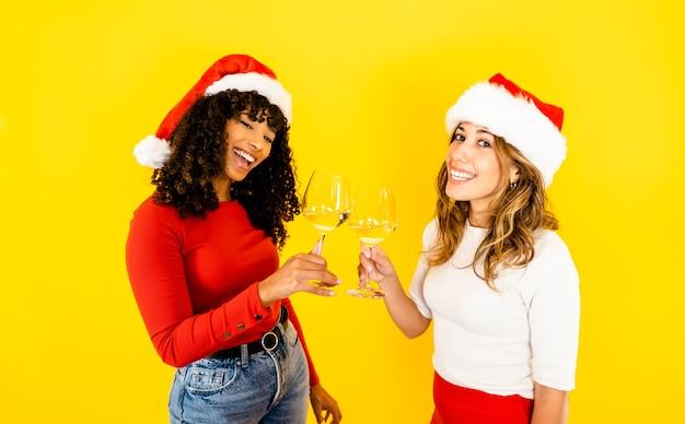 Ein schöner blonder kaukasischer toast mit ihrer schwarzen hispanischen freundin, die eine weihnachtsmütze trägt - zwei isolierte gemischtrassige frauenmodell auf gelbem wandkopierraum