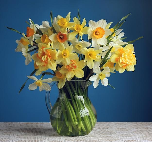 Ein schöner blumenstrauß von gelben narzissen in einem glaskrug auf dem tisch