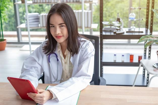 Ein schöner doktor, der einen laptop im büro verwendet