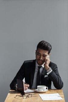 Ein schöner erfolgreicher mann, der im telefonbüro spricht und in einem notizbuch im café schreibt