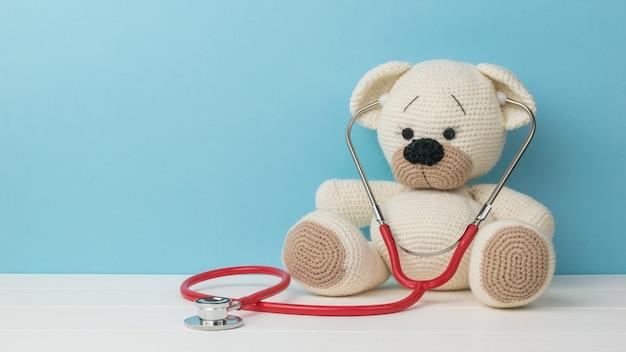 Ein schöner gestrickter teddybär mit einem stethoskop auf einem weißen tisch auf blauem grund.