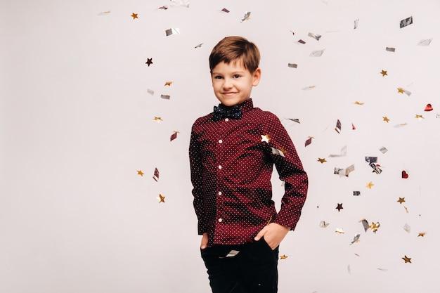 Ein schöner junge steht und konfetti fällt auf ihn auf einem grauen hintergrund