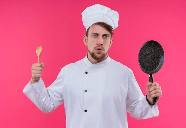 Ein schöner junger bärtiger kochmann in der weißen uniform, die kochmütze hält, die holzlöffel und bratpfanne hält, während auf einer rosa wand schaut