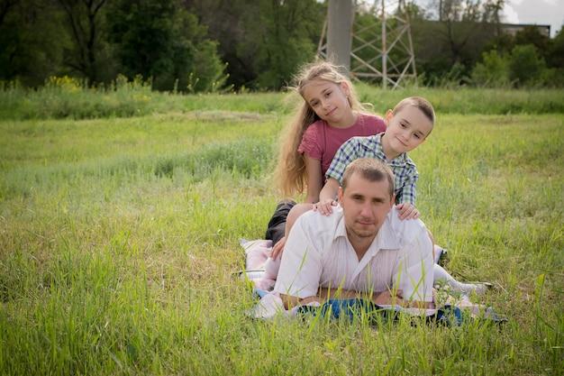 Ein schöner junger mann mit seinen kleinen kindern im park.