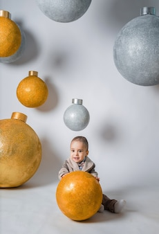 Ein schöner kleiner junge in einem hosenanzug sitzt mit einem gelben ball mit riesigen bällen. vertikale ausrichtung