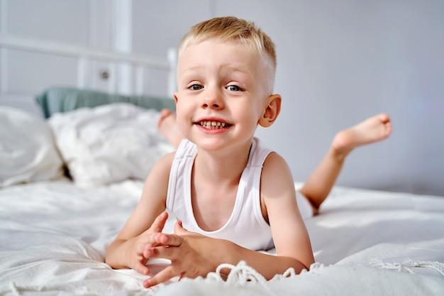Ein schöner kleiner junge mit blauen augen liegt auf dem bett.