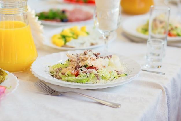 Ein schöner salat auf einem teller wird im restaurant zum abendessen oder für ein bankett serviert. im urlaub geschirr servieren