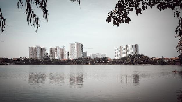 Ein schöner sonniger tag am see mit gebäuden und dem stadthintergrund