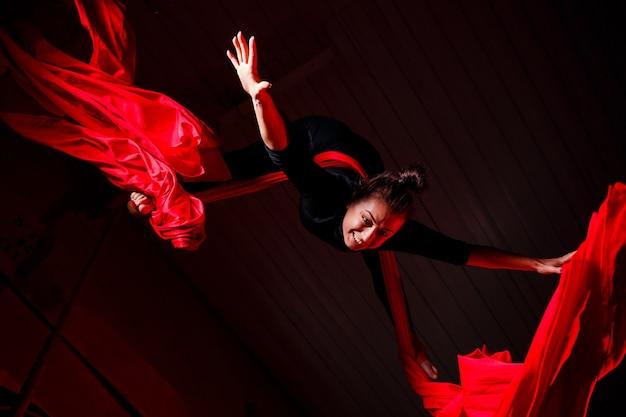 Ein schöner sportlicher mädchenakrobat führt gymnastik- und zirkusübungen auf roter seide durch. luftgymnastik auf leinwand