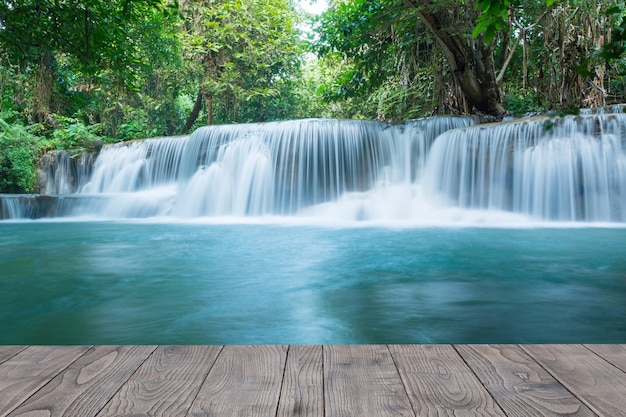 Ein schöner strom des wasserfalls im regenwald mit holzschreibtisch